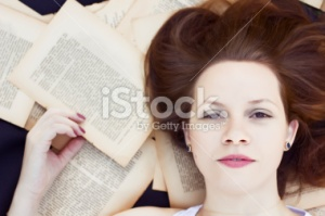 stock-photo-34925984-young-woman-lying-on-book-pages